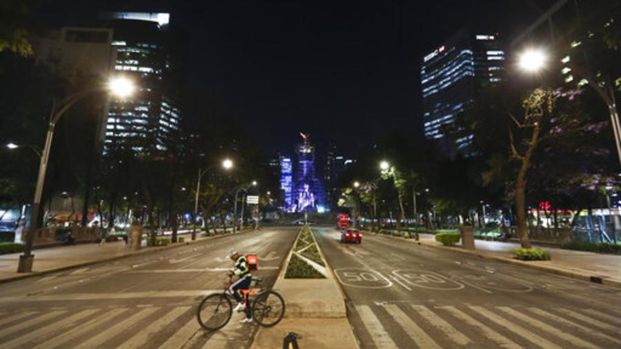 Un repartidor de comida cruza este viernes el Paseo de la Reforma en Ciudad de México, una avenida normalmente llena de tráfico.