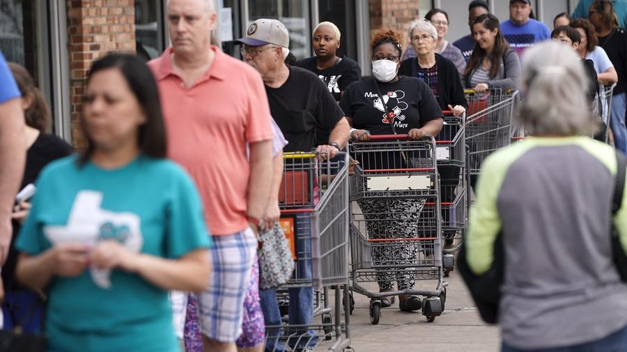 La gente espera que abra la tienda de comestibles H-E-B el martes 17 de marzo de 2020 en Spring, Texas.