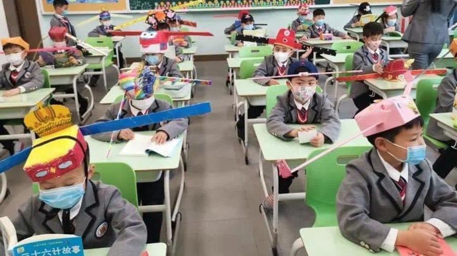 Niños en escuela de China con gorro especial para distanciamiento social