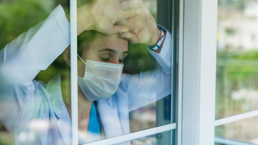 Mujer recargada en un vidrio