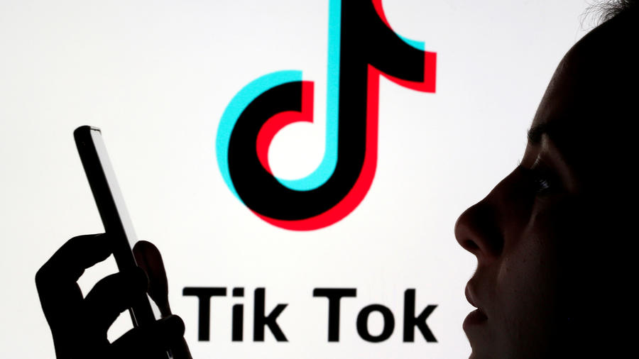 Una persona sostiene un teléfono con el logotipo de TikTok detrás.