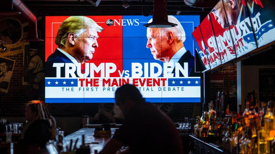 Las pantallas de televisión que transmiten el primer debate presidencial entre Trump y Biden en Walters Sports Bar el 29 de septiembre en Washington, D.C.