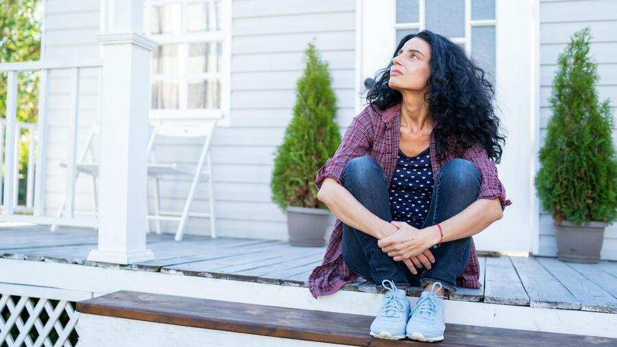 Mujer sentada frente a su casa
