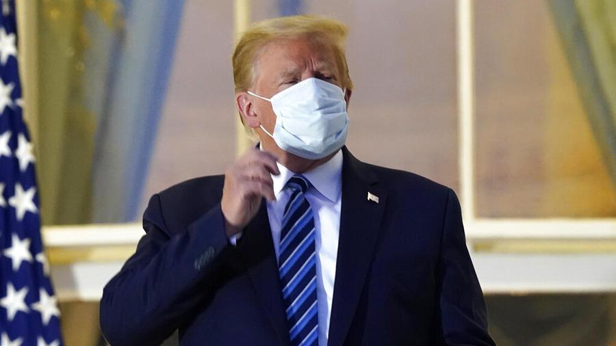 El presidente, Donald Trump, a punto de quitarse la mascarilla al regresar a la Casa Blanca tras ser hospitalizado por COVID-19.
