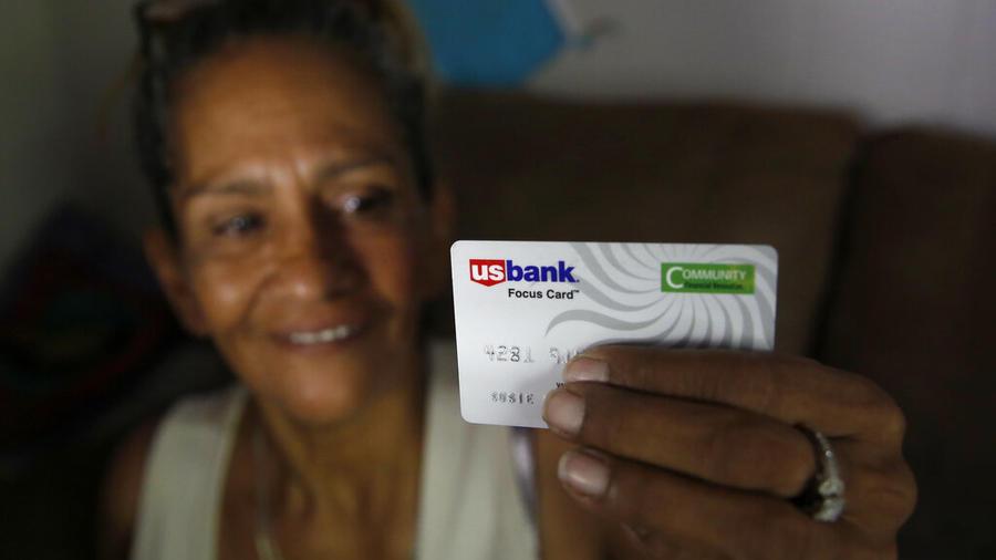 Una de las beneficiarias de un programa de renta universal en California recibe una tarjeta de débito.