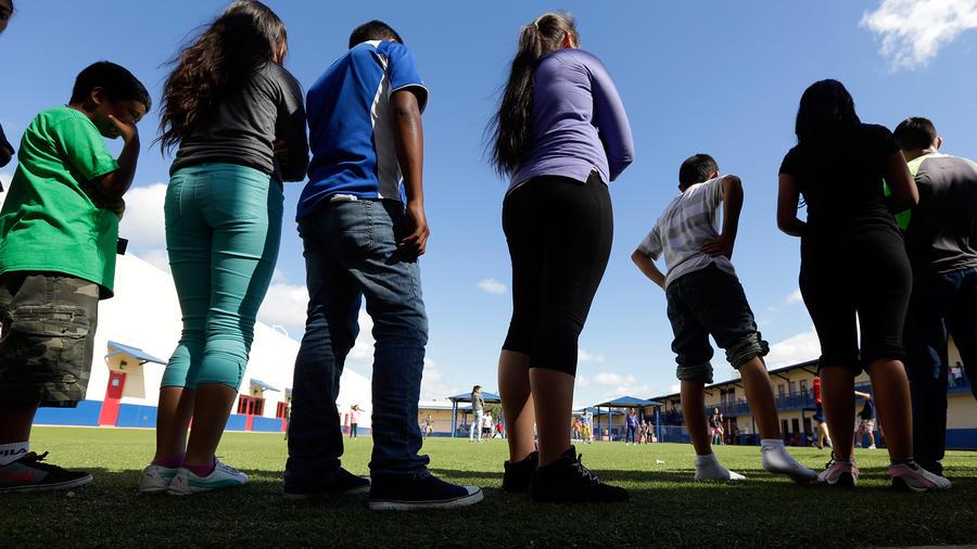 Menores indocumentados que cruzaron solos hacen una fila en un albergue de EEUU.