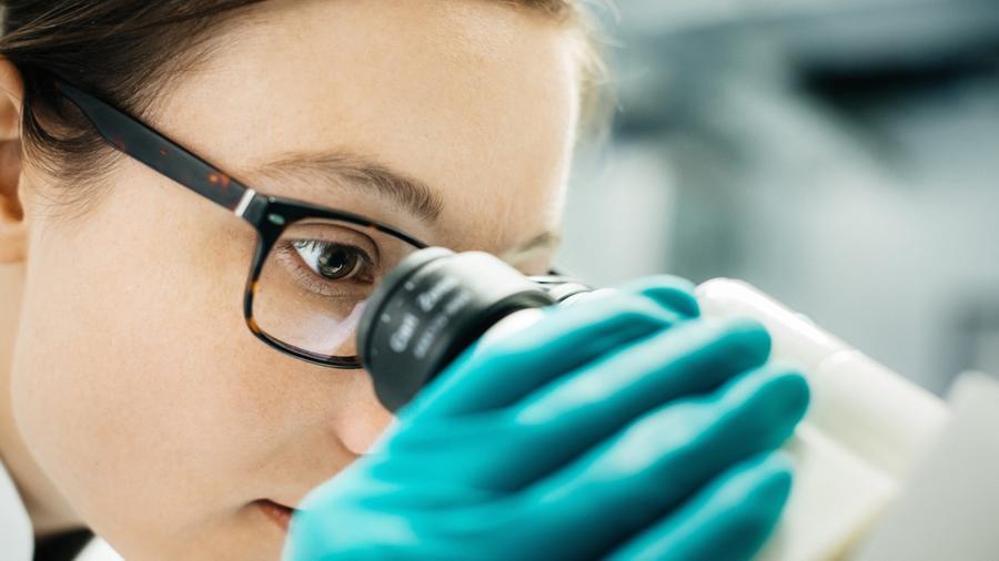 Científica mirando microscopio