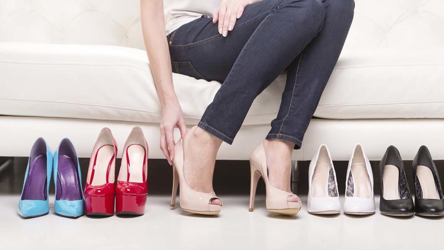mujer sentada junto a una fila de zapatos, probando un par