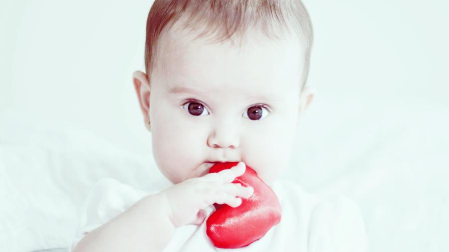 Bebé con juguete en forma de corazón