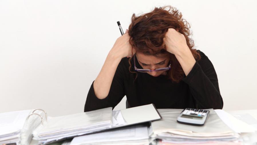 Mujer preocupada con documentos en escritorio