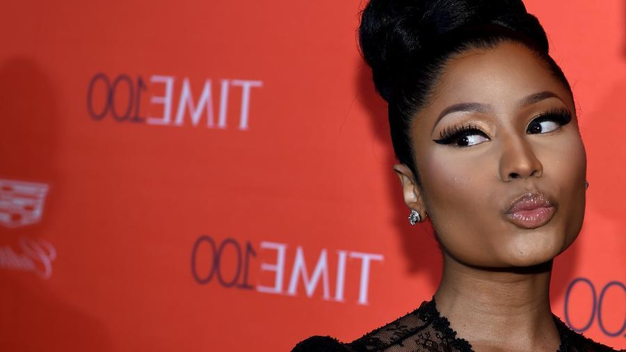 Nicki Minaj posando frente a un fondo rojo