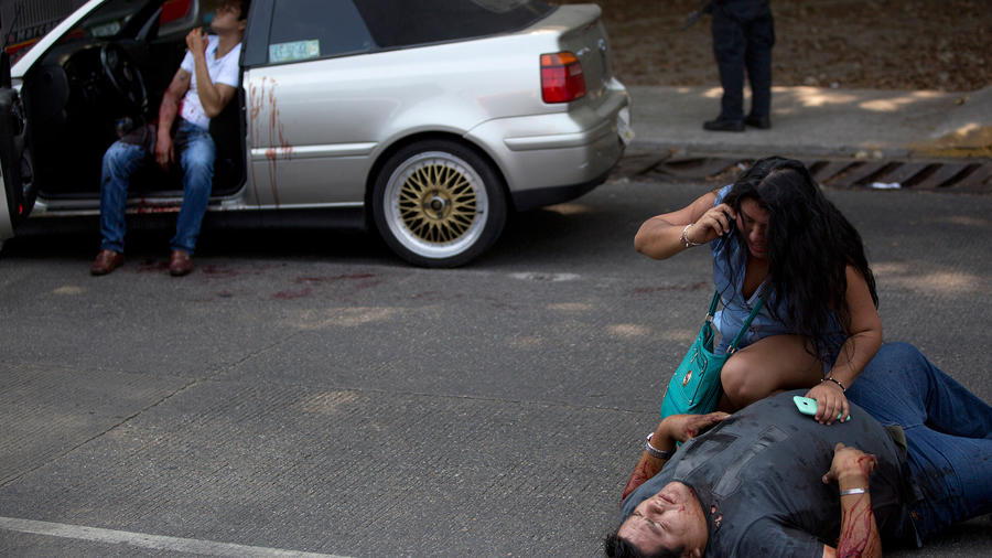 En esta foto del 13 de mayo de 2016, una mujer conversa por teléfono frente a una persona herida, Edgar Osvaldo Vega, mientras Pedro Gracias permanece herido y sentado en un vehículo en espera de ayuda después de que los balearan mientras viajaban en auto