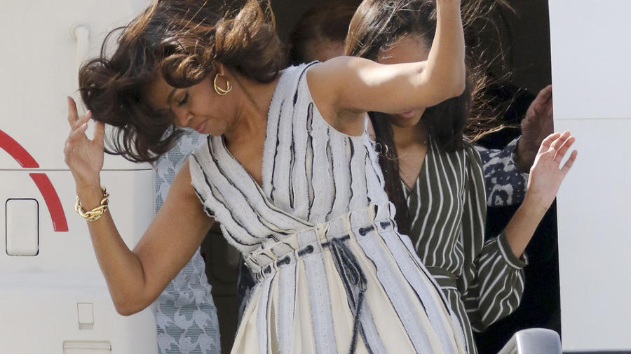 Michelle Obama y sus hijas, contra el viento, bajan del avión en España