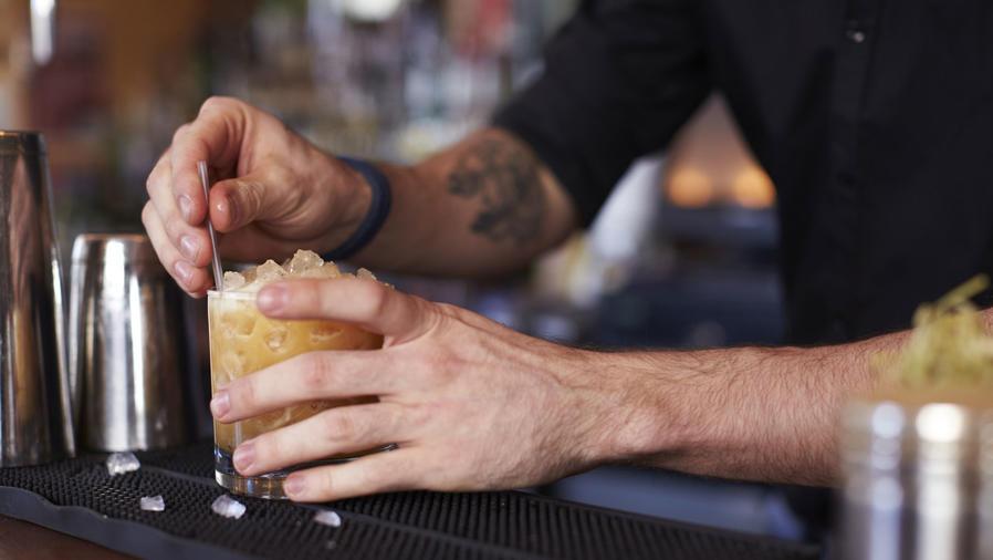 Bartender sirviendo un cóctel en un vaso corto