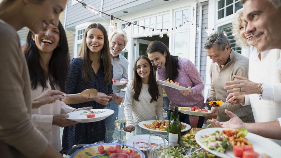 Familia hispana sirviendo comida estilo buffet en el patio