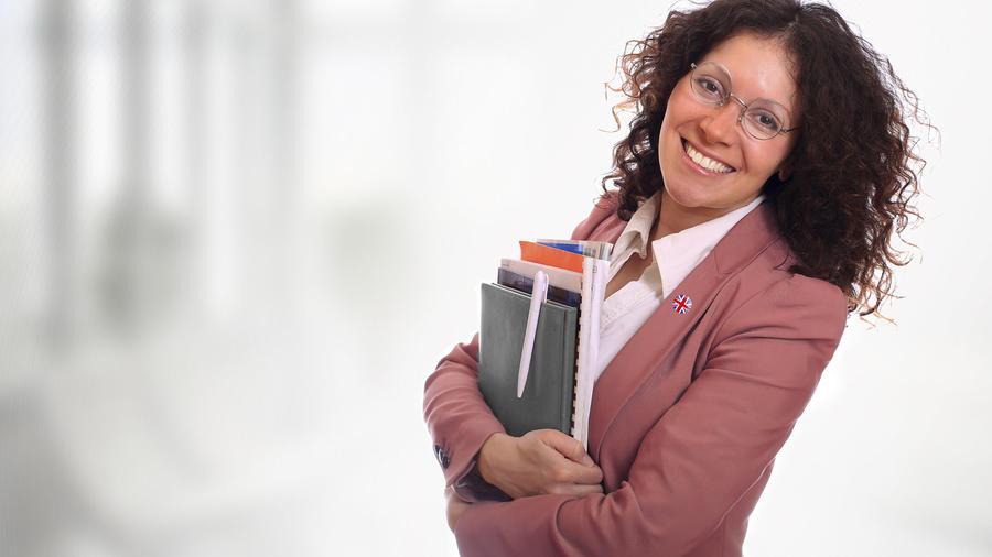 Maestra con gafas y cuadernos sonriendo