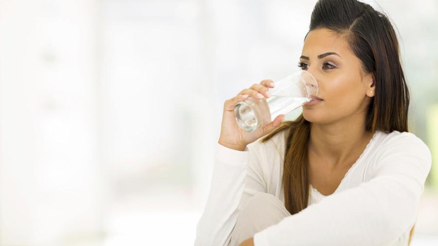 Mujer joven en pijamas bebiendo agua