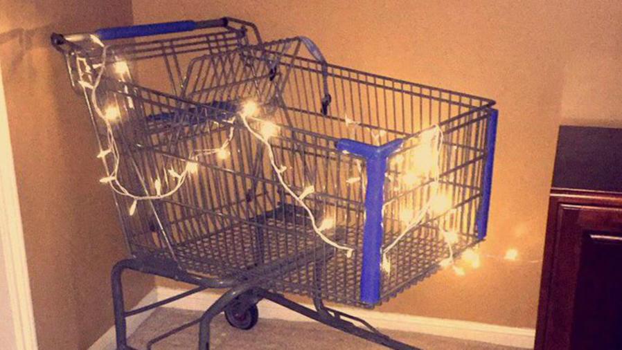 Carrito de supermercado envuelto en luces navideñas.