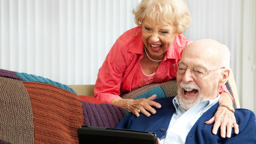 Pareja de ancianos ríe con Tablet