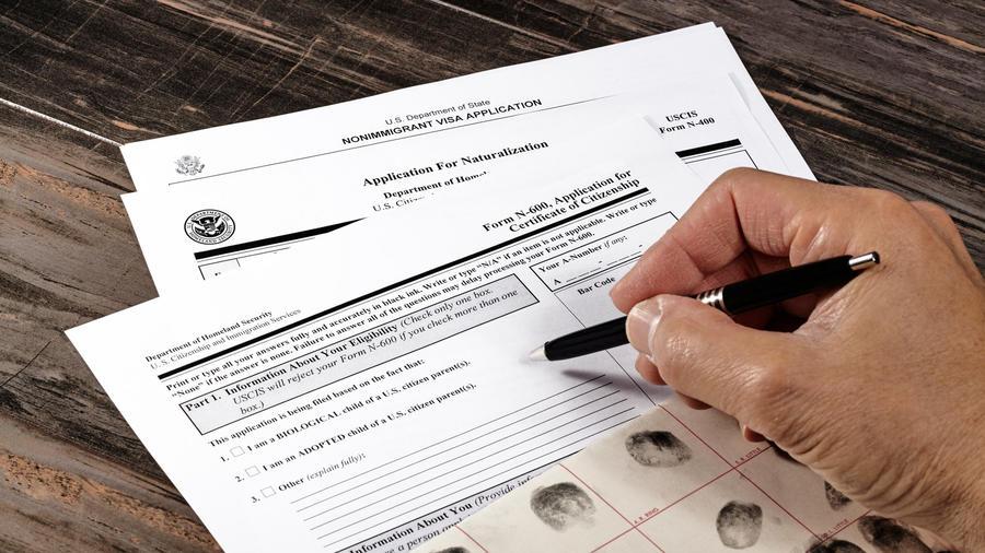 Foto de archivo: Persona llenando un formulario para trámitesmigratorios