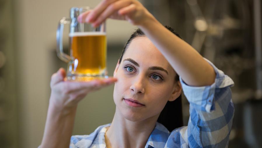 Mujer revisando vaso de cerveza