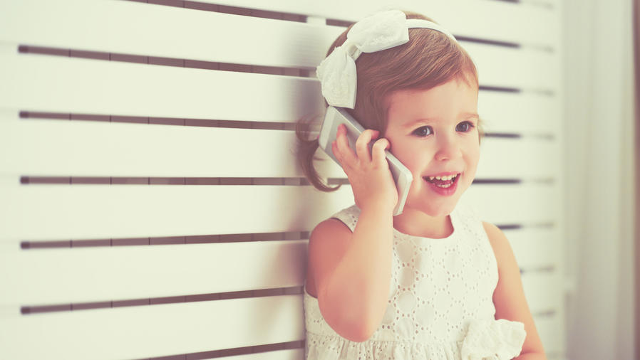 Niña pequeña jugando con un teléfono móvil