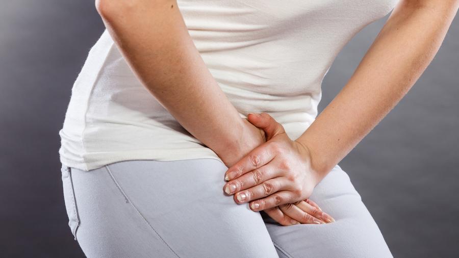 Mujer cubriéndose la entrepierna con las manos