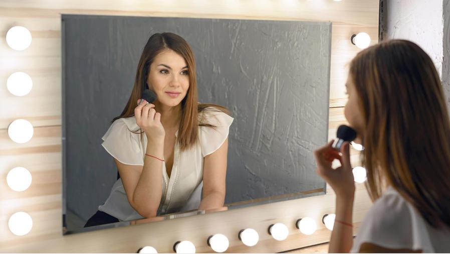 Mujer maquillándose frente al espejo.
