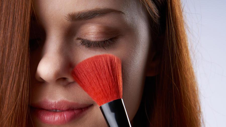 Mujer se maquilla con pincel.