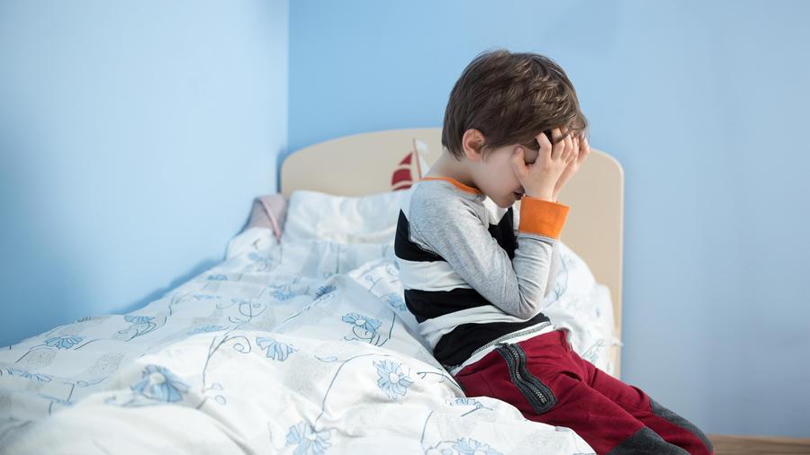 Niño triste sentado en la cama