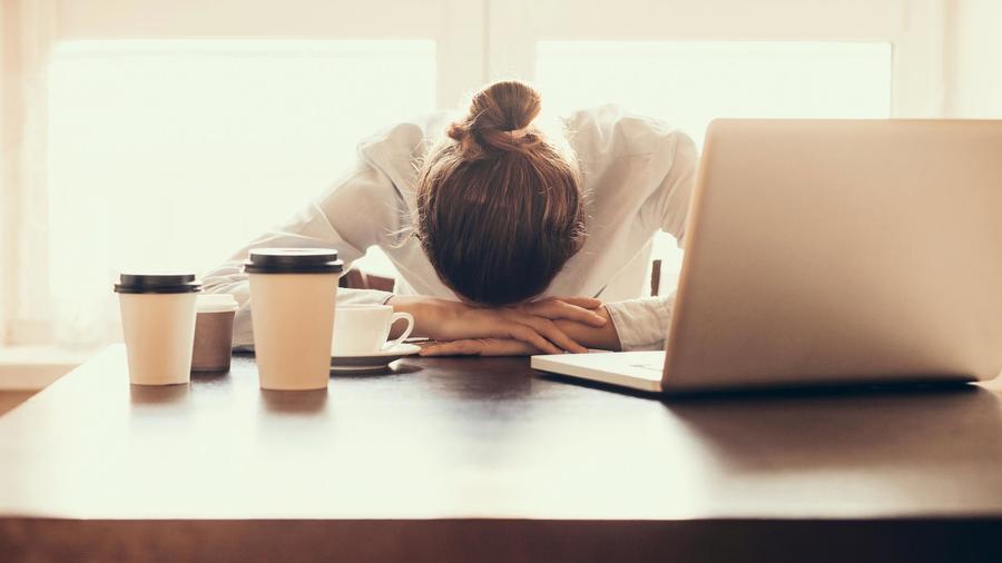 Mujer frustrada con la cabeza apoyada en el escritorio