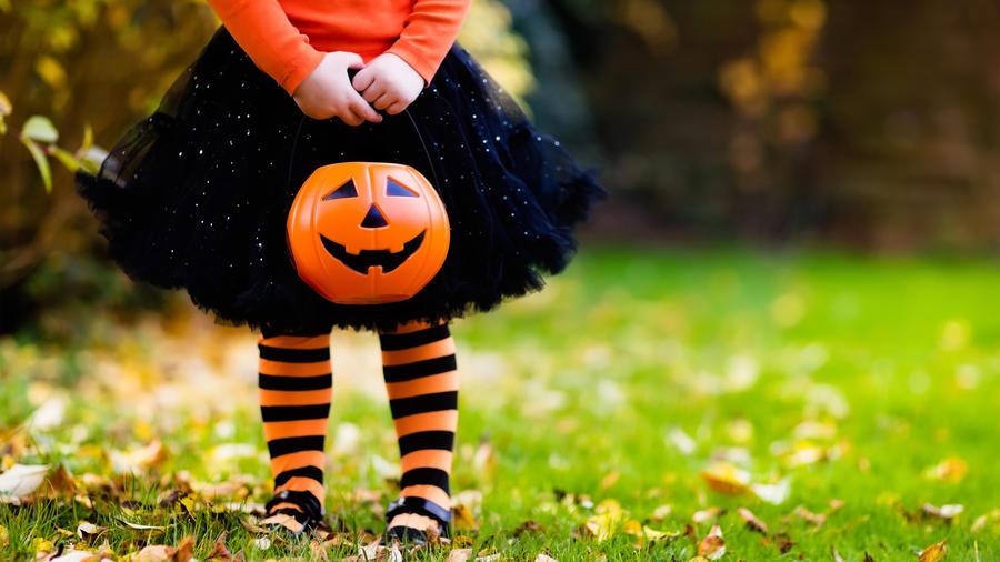 Niña con disfraz pidiendo dulces en Halloween