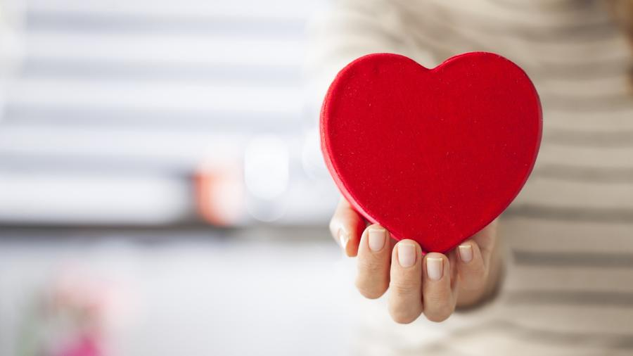 Mujer sosteniendo corazón rojo