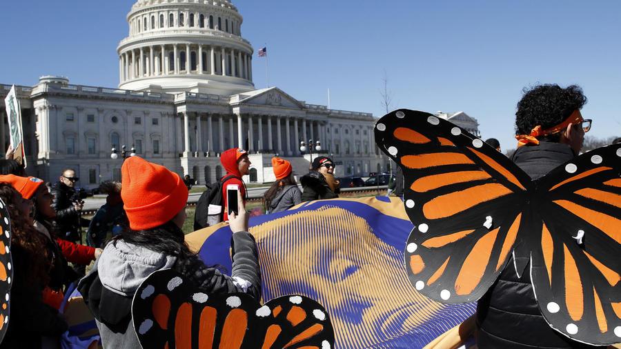 """Usando """"alas de mariposa"""", los partidarios de DACA sostienen una lona con una imagen del presidente Donald Trump en una manifestación."""