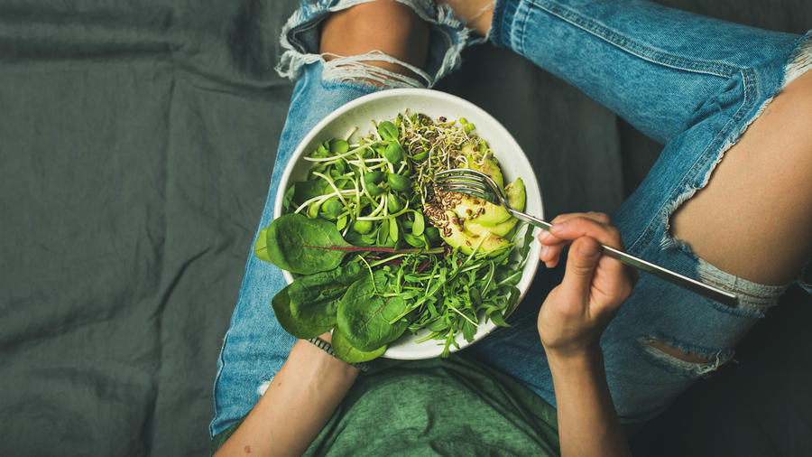 Mujer comiendo una porción de espinaca