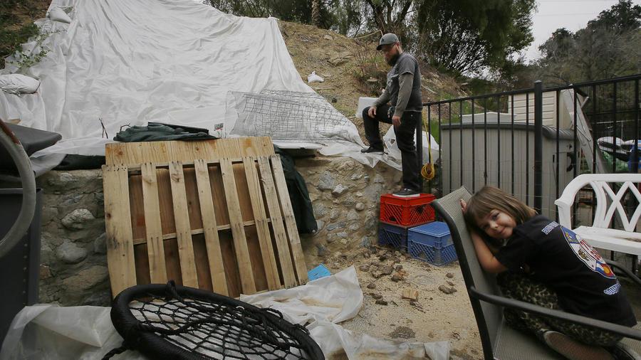 Andrew Joos-Visconti trabaja para proteger su patio trasero de las próximas lluvias con una lona de plástico, en el área de Sun Valley, en Los Ángeles, el martes 20 de marzo de 2018.