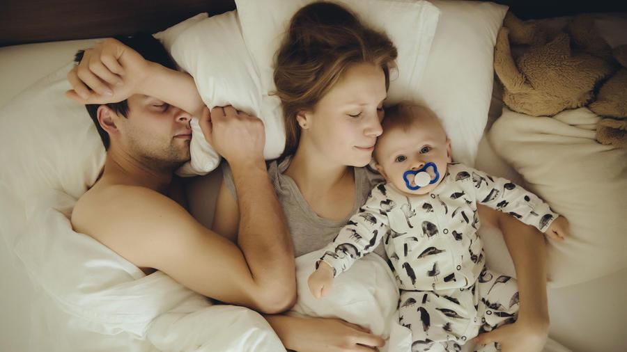 Pareja con su bebé en la cama
