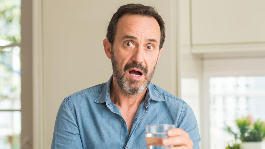 Hombre sorprendido bebiendo agua