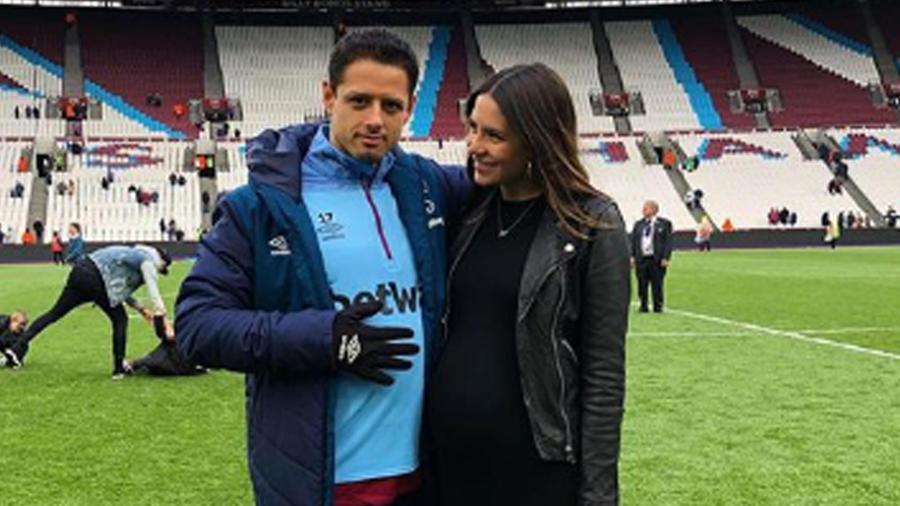 """Sarah Kohan y Javier """"Chicharito"""" Hernández posando juntos en la cancha de futbol"""