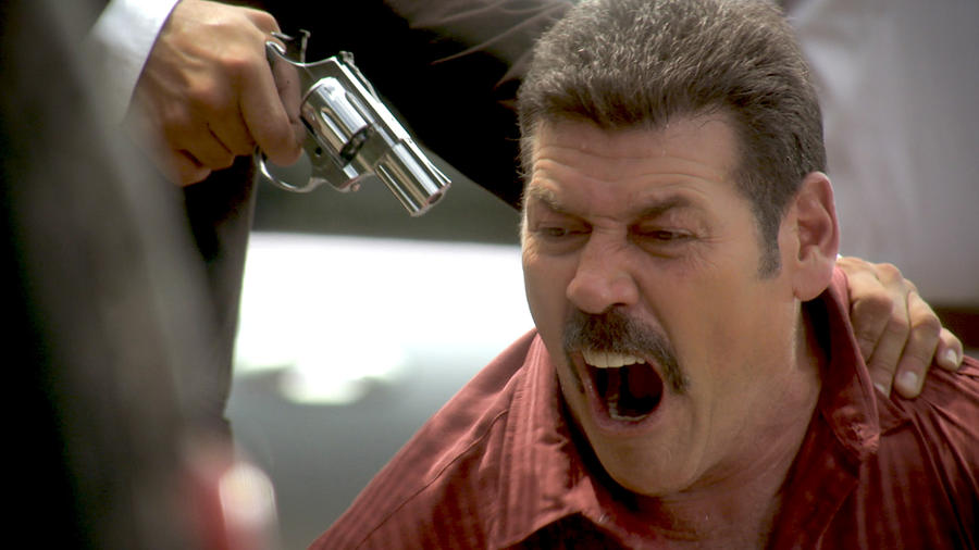 Guillermo Quintanilla gritando mientras lo apuntan con un arma en Tierra de Reyes