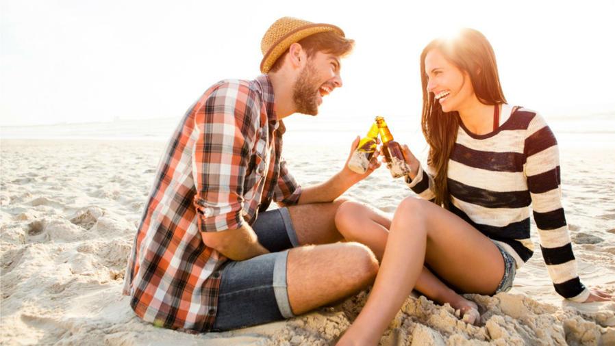 Pareja tomando cerveza en la playa
