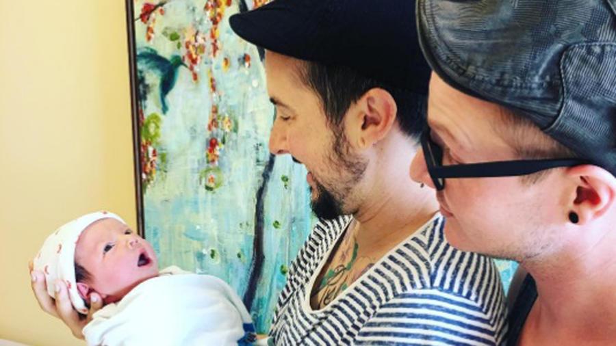 Trystan Reese y Biff Chaplow cargando a su bebé