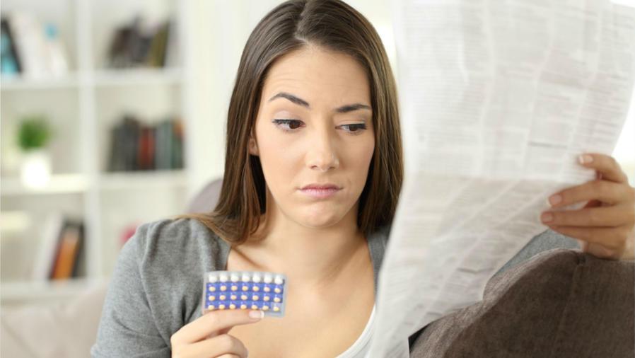 Mujer leyendo el instructivo de la píldora anticonceptiva