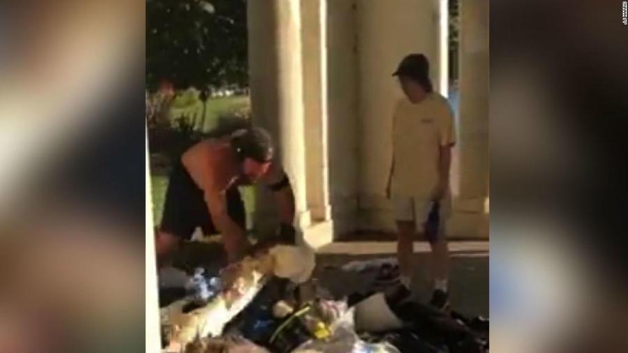 Hombre tirando las cosas de un sin techo