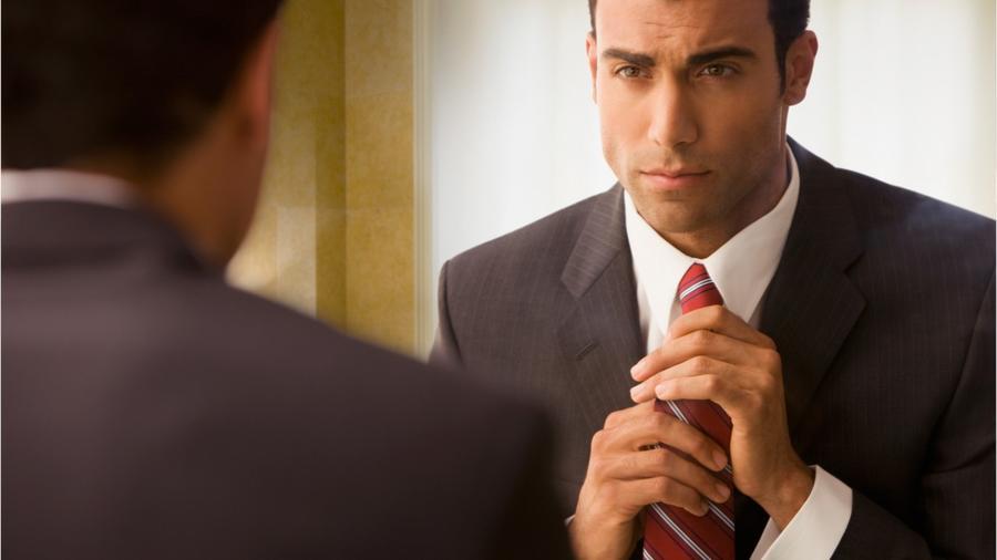 Hombre se arregla la corbata frente al espejo