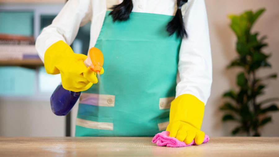Mujer desinfectando mueble