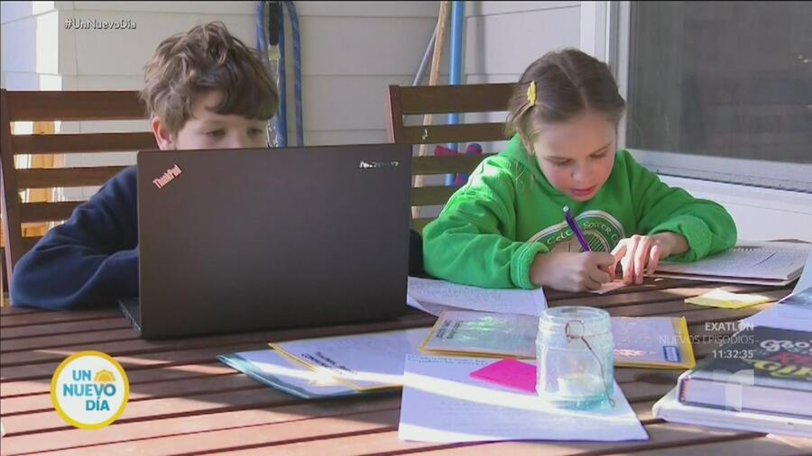 Niño usando computadora y niña escribiendo