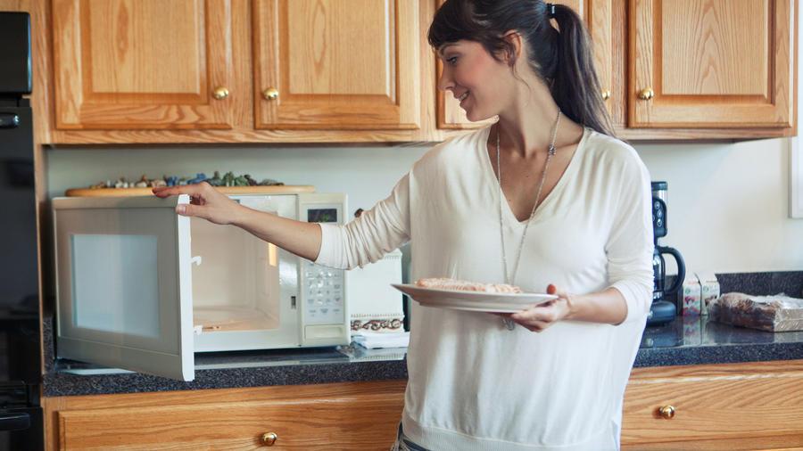 Mujer usando el microondas