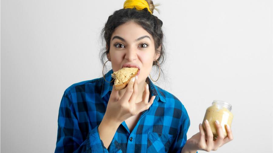 Mujer comiendo un pan con mantequilla de maní