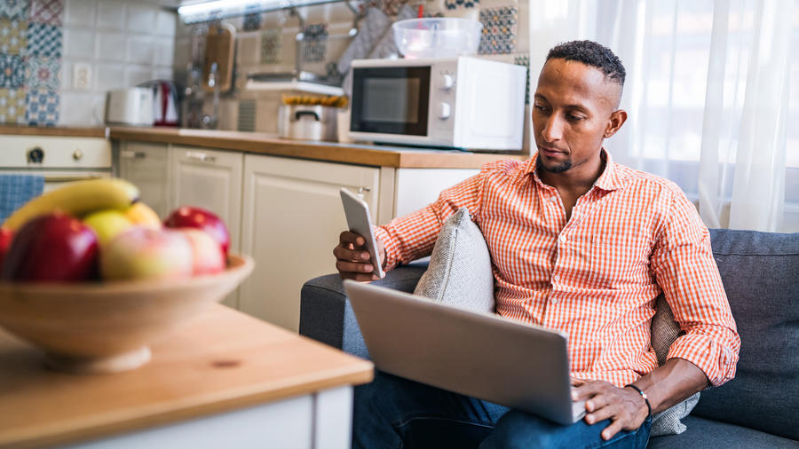 Man checking phone with laptop on him
